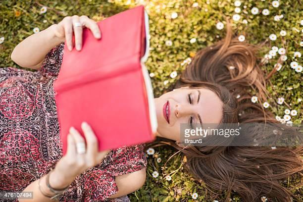 Vista de arriba de mujer joven lee un libro en la hierba.