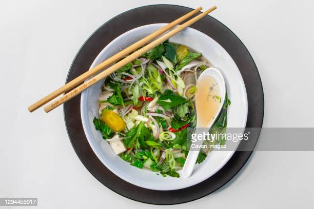 above-view of bowl of asian noodle soup with chopsticks and spoon - pho soup stock pictures, royalty-free photos & images