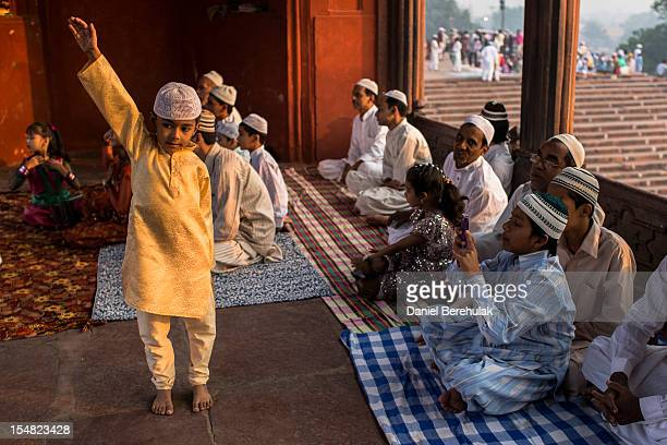 Aboy poses for a photograph being taken by a family member as Indian Muslims gather for Eid alAdha prayers at Jama Masjid on October 27 2012 in New...