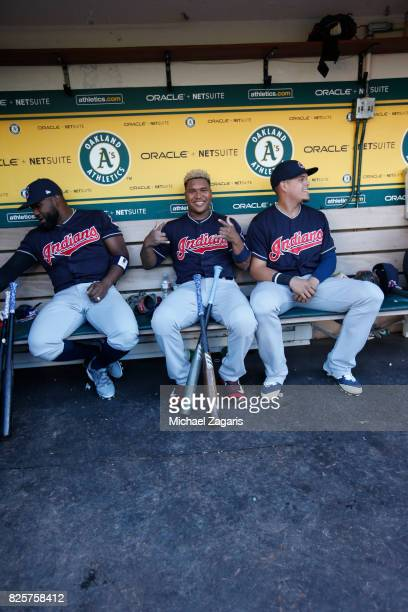 Abraham Almonte Jose Ramirez and Brandon Guyer of the Cleveland Indians sit in the dugout prior to the game against the Oakland Athletics at the...