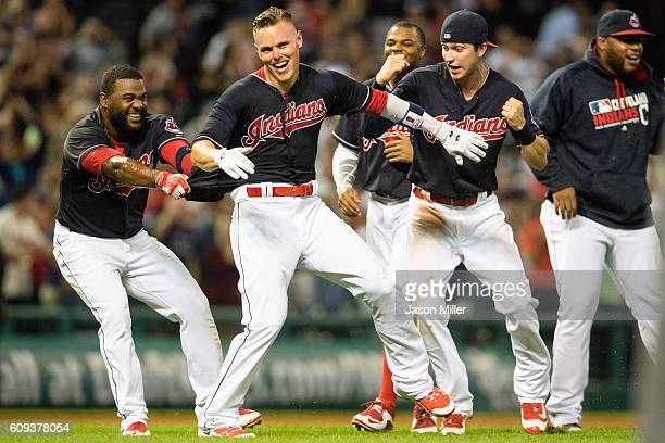 Abraham Almonte of the Cleveland Indians celebrates with Brandon Guyer and Tyler Naquin after Guyer hit a walkoff RBI double to defeat the Kansas...