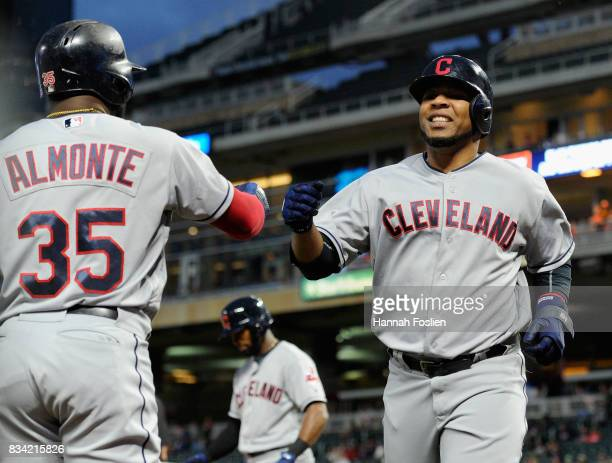 Abraham Almonte of the Cleveland Indians congratulates teammate Edwin Encarnacion on scoring a run against the Minnesota Twins during the seventh...
