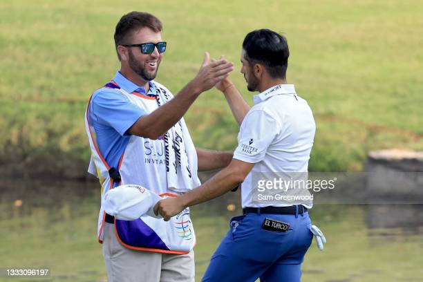 Abraham Ancer of Mexico and his caddie celebrate after winning the FedEx St. Jude Invitational after the second playoff hole at TPC Southwind on...