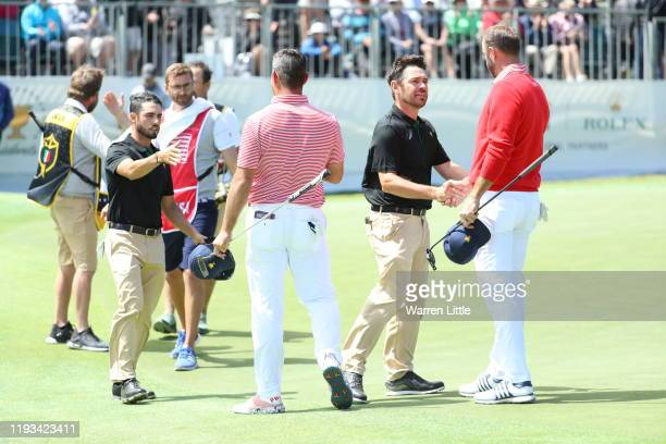 Abraham Ancer of Mexico and the International team and Louis Oosthuizen of South Africa and the International team shake hands with Gary Woodland of...