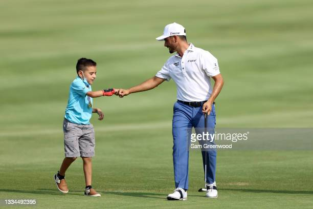 """Abraham Ancer of Mexico """"fist bumps"""" with a fan on the 18th hole during the final round of the World Golf Championship-FedEx St Jude Invitational at..."""