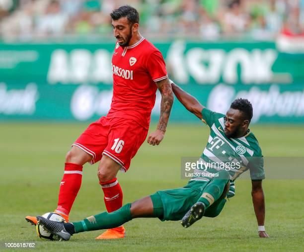Abraham Frimpong of Ferencvarosi TC slide tackles Nikolaos Ioannidis of DVTK during the Hungarian OTP Bank Liga match between Ferencvarosi TC and...