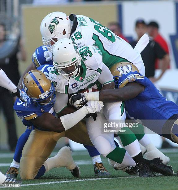 Abraham Kromah of the Winnipeg Blue Bombers stops Will Ford of the Saskatchewan Roughriders as he tries to gain yards in first half action in a CFL...