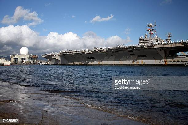 uss abraham lincoln, cvn 72, after participating in the multi-national exercise rimpac, is towed into pearl harbor and approaches the sea based x-band radar undergoing service at the pearl harbor shipyard. - pearl harbor naval shipyard stock photos and pictures