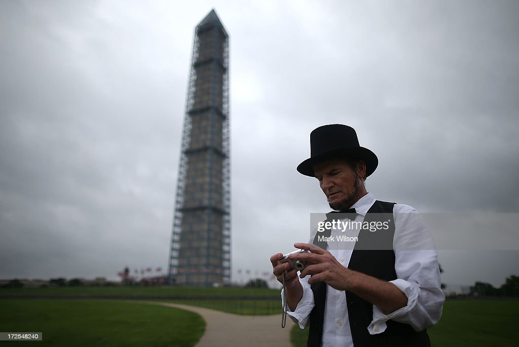 Abraham Lincoln imperonator Johnny Schuler looks at his camera while attending a toy gun during a rally on the grounds of the Washington Monument July 3, 2013 in Washington, DC. Gun rights advocates participates in the Armed Toy Gun March on D.C. to raise money and toys for the Toys for Tots program.