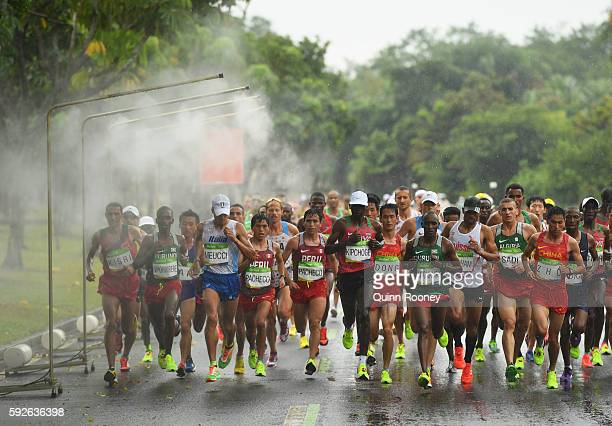 Abraham Niyonkuru of Burundi and Eliud Kipchoge of Kenya lead the pack as they race past a cooling station during the Men's Marathon on Day 16 of the...