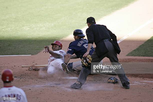 Abraham Nunez of the St Louis Cardinals scores ahead of the tag by Ramon Hernandez during action against the San Diego Padres during Game 2 of the...