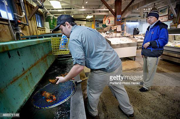 Abraham Turcotte of Harbor Fish Market in Portland takes lobsters out of the lobster tank for Phillip Yang of Cranston Rhode Island Thursday March 5...