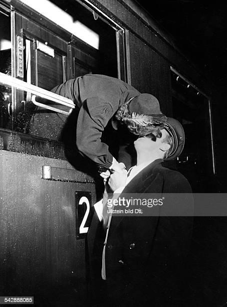 Abschiedsszene am Bahnhof eine Frau beugt sich aus dem Zugfenster und verabschiedet sich mit einem Kuss von einem Mann der auf dem Bahnsteig steht...