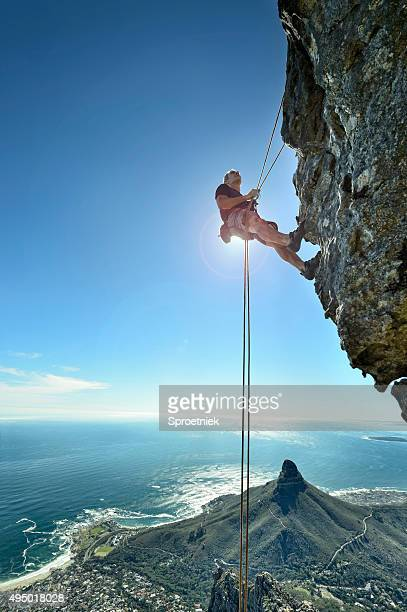 Abseiling climber over precipice looks up at rock face