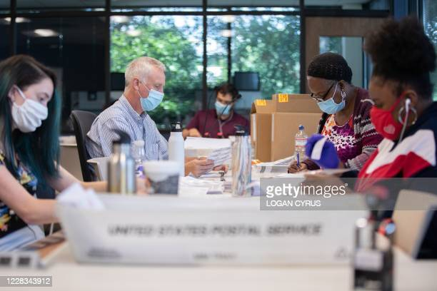 Absentee ballot election workers stuff ballot applications at the Mecklenburg County Board of Elections office in Charlotte, North Carolina on...