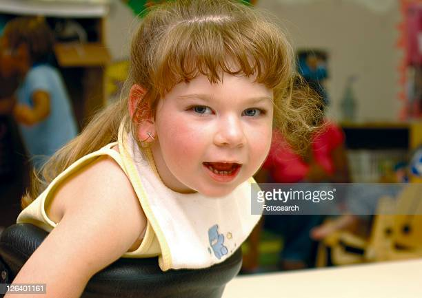 absolutely adorable blond-haired little girl, smiling, while using an adaptive standing device at her developmental day program. - cerebrum stock photos and pictures