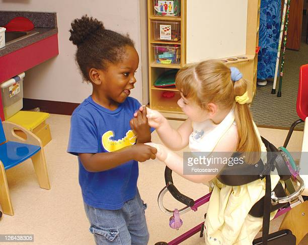 absolutely adorable image of two friends, one with multiple disabilities, one with none, interacting in a classic little girl game as they play together at school. - cerebrum stock pictures, royalty-free photos & images