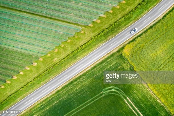 abstrakte landwirtschaftliche felder, gemüseplantage und straße-luftaufnahme - ollo stock-fotos und bilder