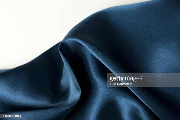 abstract background of a luxurious blue fabric wavy folds of a silk texture of a satin material on a white background. classic blue luxurious background with copy space. - silk stock pictures, royalty-free photos & images