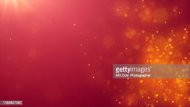 abstract background of de-focused gold colored particles on red background with lens flare - glamour stock-fotos und bilder