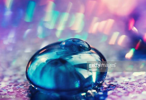 Abstract blue glass ball with drop on violet background