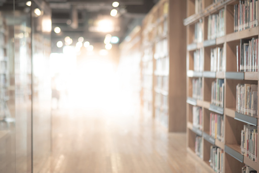 Abstract blurred public library interior space. blurry room with bookshelves by defocused effect. use for background or backdrop in business or education concepts 1132077472