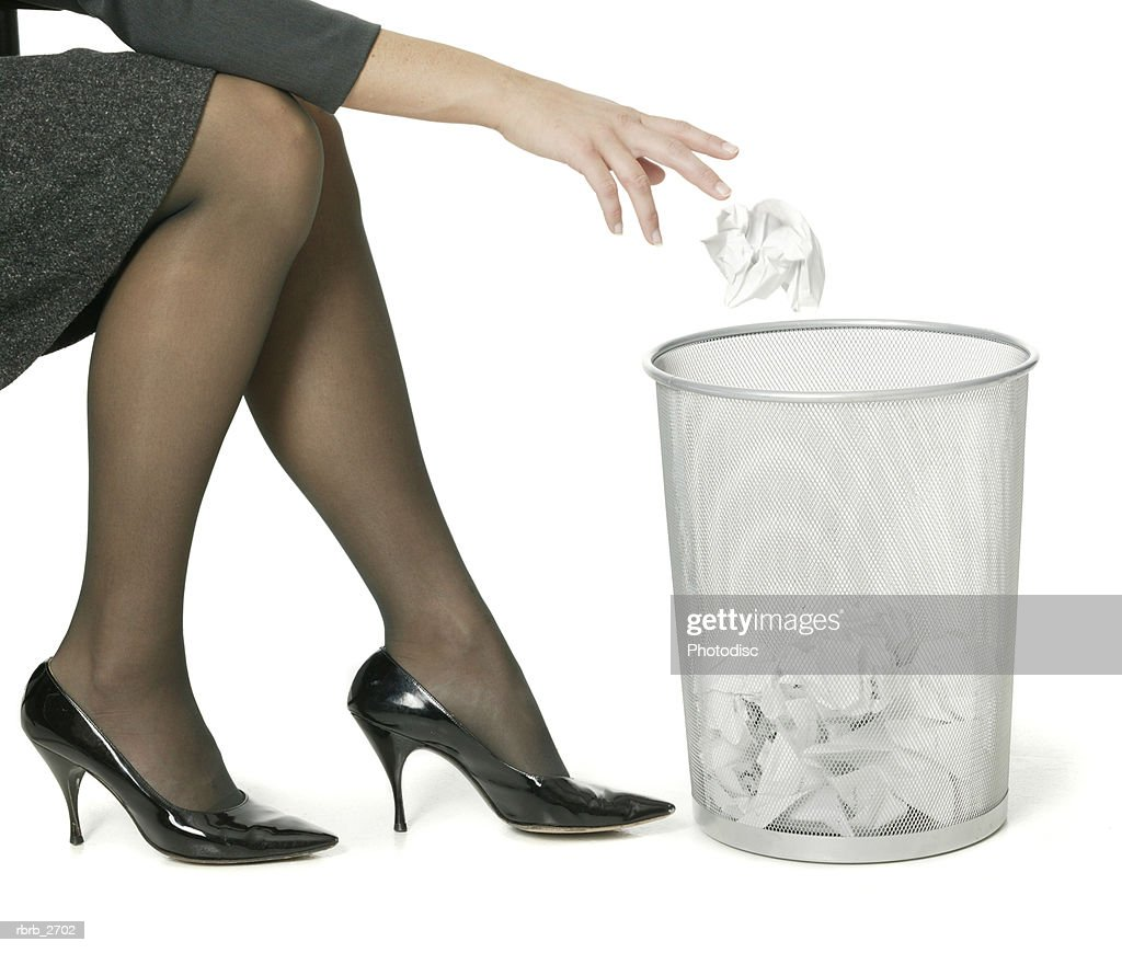abstract business shot of a young adult woman as she show her legs while tossing trash : Foto de stock