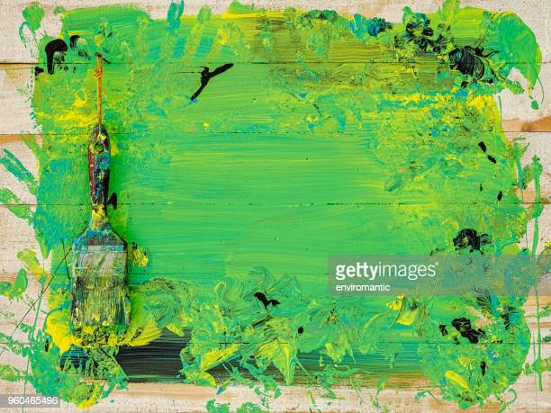 Abstract colorful paint background with a paintbrush hanging on a nail on an old wooden plank wall.