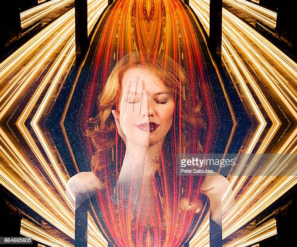 Abstract composite portrait of young woman with hand on eye and highway traffic and light trails