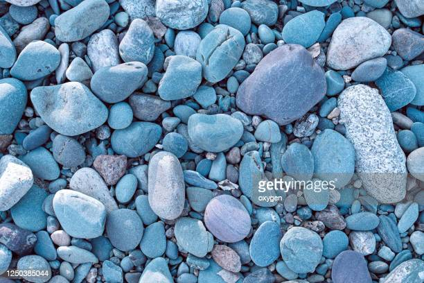 abstract dry pebbles stones blue toned background - rock stock pictures, royalty-free photos & images