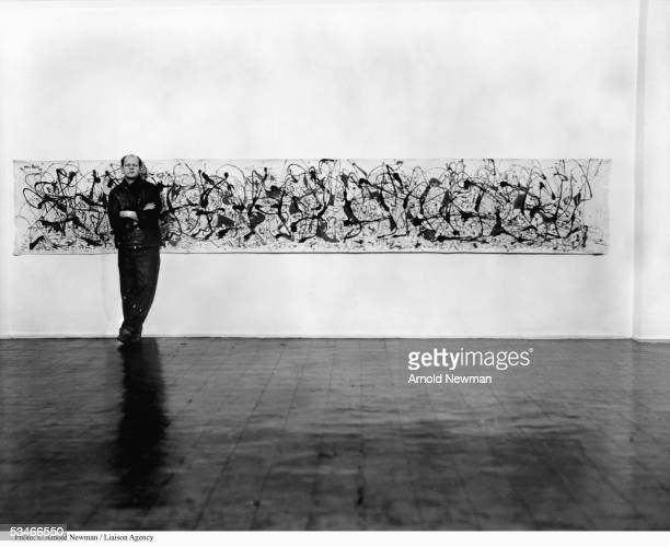 Abstract Expressionist painter Jackson Pollock poses for portrait next to painting January 3 1949 in New York
