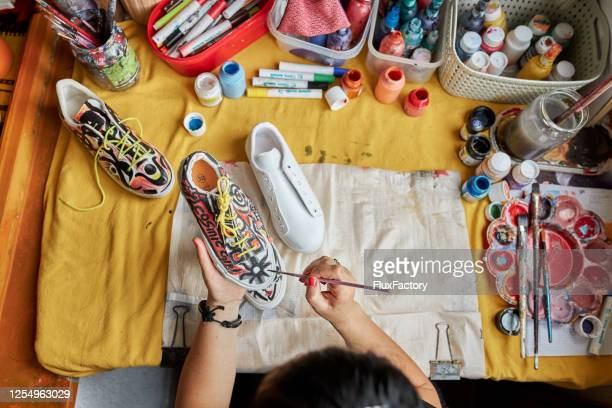 abstract female artist painitng sneakers in a colorful way - tempera painting stock pictures, royalty-free photos & images