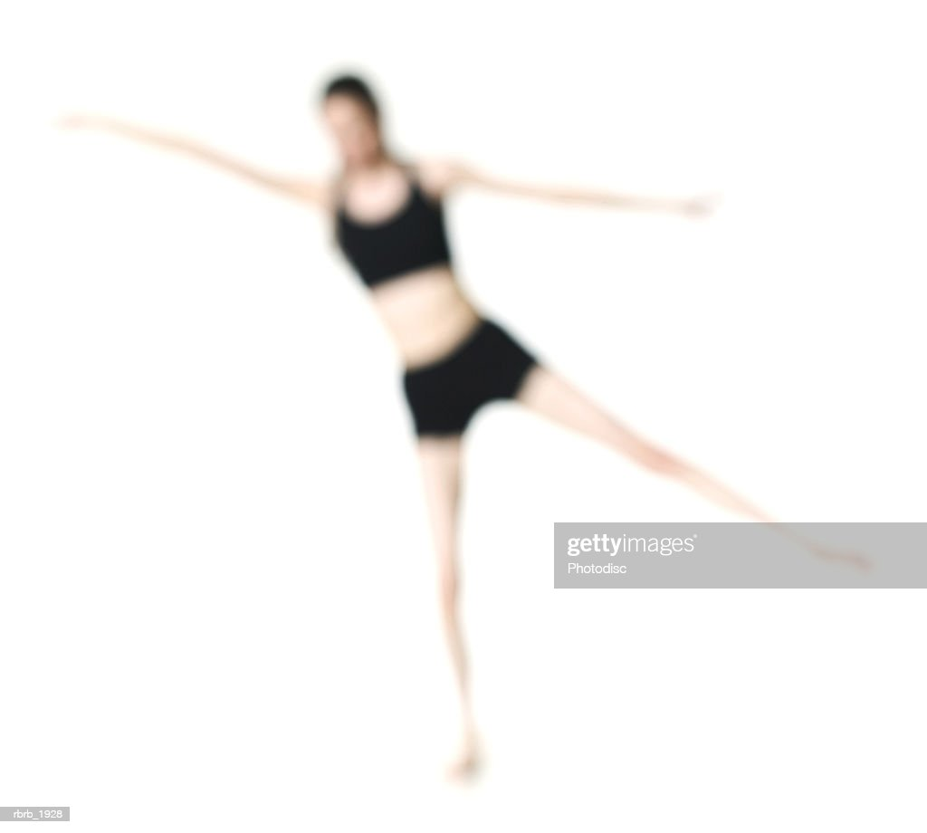 abstract full body shot of a young adult in a workout outfit as she stretches out : Stockfoto