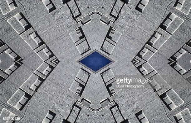 Abstract image: kaleidoscopic image of facade of industrial building with walled windows painted in white
