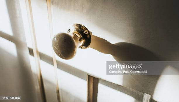 abstract image of an old door knob casting a shadow on an old wooden door - turning stock pictures, royalty-free photos & images
