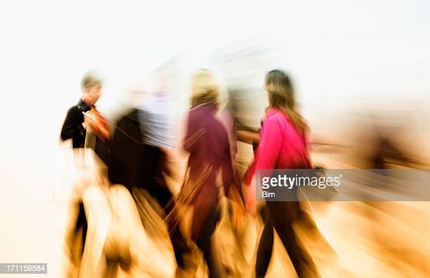 抽象的な画像のぼやけた動きカラフルな服装の人々のウォーキング高速