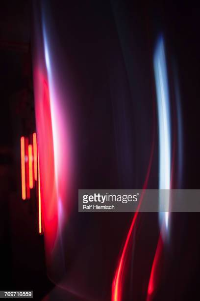 Abstract image of red and gray light trails over black background