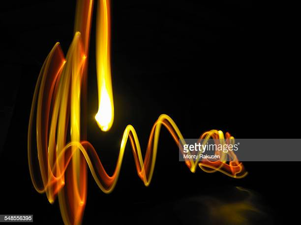 Abstract light trails made by molten metal against black background