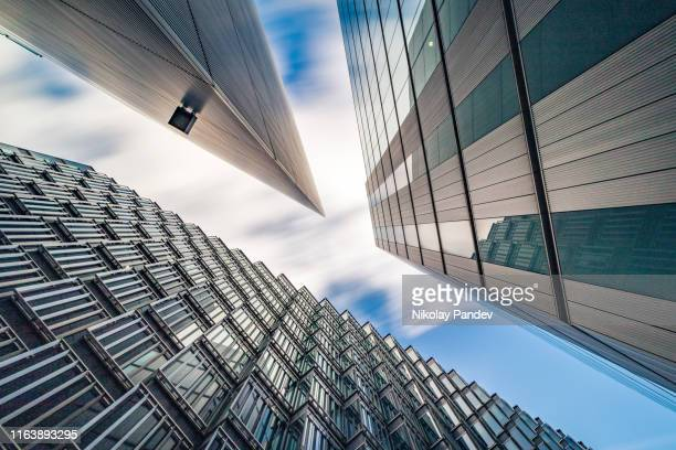 abstract low and wide angle view up towards modern business buildings in london's financial district - creative stock image - cityscape stock pictures, royalty-free photos & images