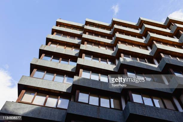 abstract low angle view of black building with symmetrical window rows - arquitectura exterior fotografías e imágenes de stock
