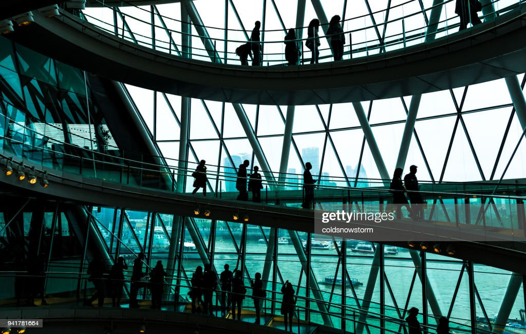 Abstract modern architecture and silhouettes of people on spiral staircase : Stock Photo
