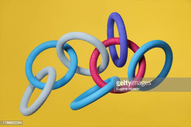 abstract multi-colored objects levitation in mid air on yellow background - chain stock pictures, royalty-free photos & images