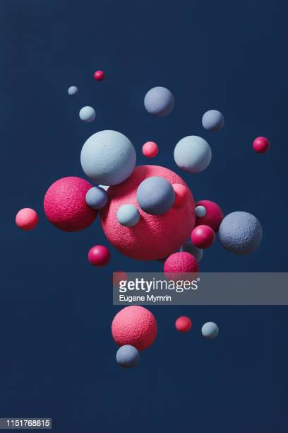 abstract multi-colored spheres on dark blue background - atomic imagery stock pictures, royalty-free photos & images