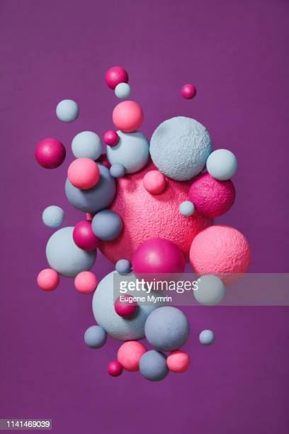 abstract multi-colored spheres on purple background - molecules stock photos and pictures