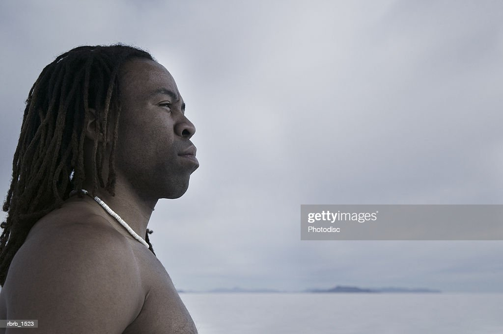 abstract photograph of a shirtless african american man as he looks out over a vast plain of nothingness : Stockfoto