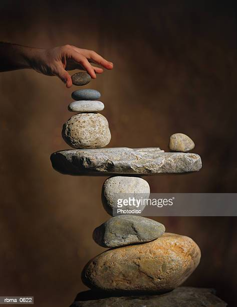 abstract photograph of hands trying to carefully balance a pile of rocks
