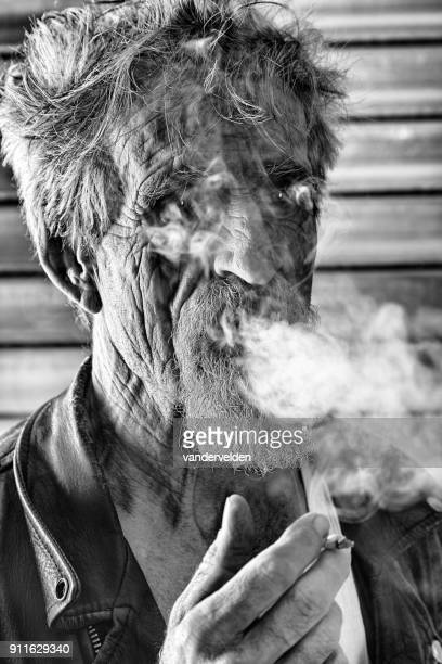 abstract portrait of an older man smoking - industrial door stock pictures, royalty-free photos & images
