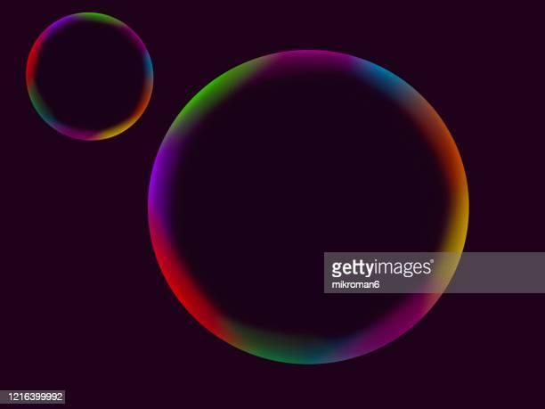 abstract rainbow spheres on black background - blase physikalischer zustand stock-fotos und bilder