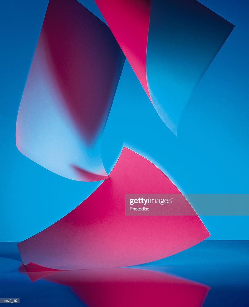 abstract red and blue colored papers fall to a reflective surface : Stockfoto