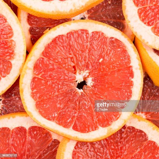 abstract red background with citrus-fruit of grapefruit slices. close-up - juicy stock pictures, royalty-free photos & images